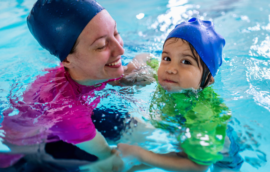 mom holding child in pool
